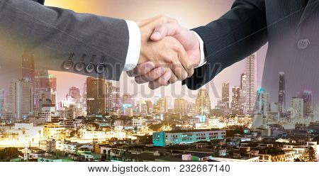 Business People Shaking Hands With Double Exposure View Night Time Of The City.