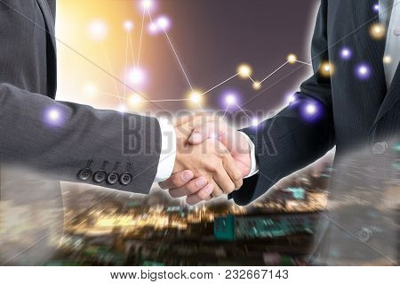 Business People Shaking Hands With Double Exposure View Night Time Of The City.  Connection Concept.