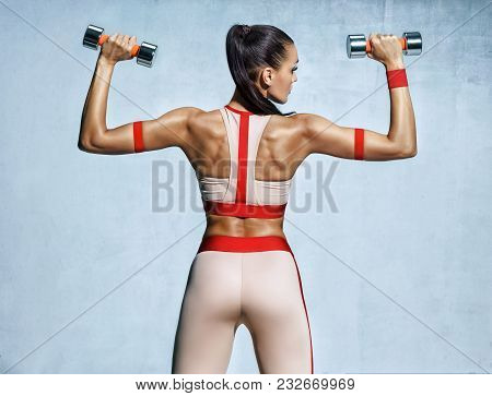 Athletic Woman Doing Exercise For Arms. Photo Of Muscular Fitness Model Working Out With Dumbbells O