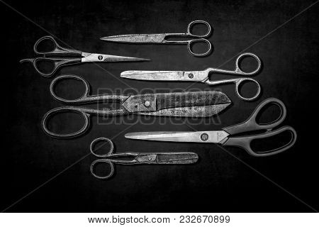 Group Of Various Scissors Isolated On Dark Background