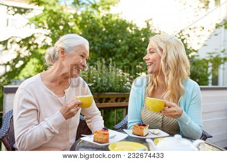 family, generation and people concept - happy smiling young daughter with senior mother drinking tea at cafe or restaurant terrace