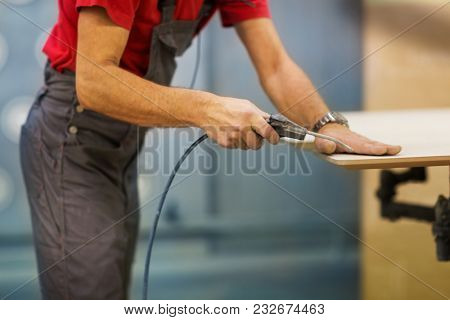 production, manufacture and woodworking industry concept - worker with glue gun and board at furniture plant workshop