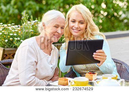family, technology and people concept - happy smiling young daughter with tablet pc computer and senior mother at cafe or restaurant terrace