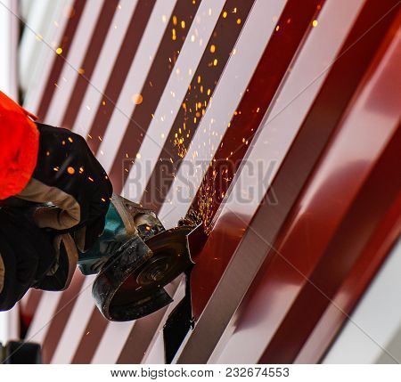 Selective Focus At Steel Cutter. Man Use Electric Steel Cutter And Clamp Metal And Throwing Many Sha