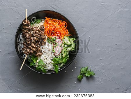Power Balanced Buddha Bowl. Asian Style Beef Skewers, Rice Vermicelli, Pickled Vegetables Salad Carr