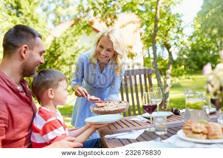 leisure, family and people concept - happy mother, father and little son eating pie at festive dinner or summer garden party