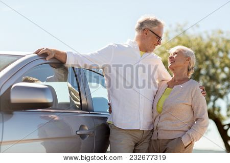 road trip, travel and old people concept - happy senior couple with car in summer