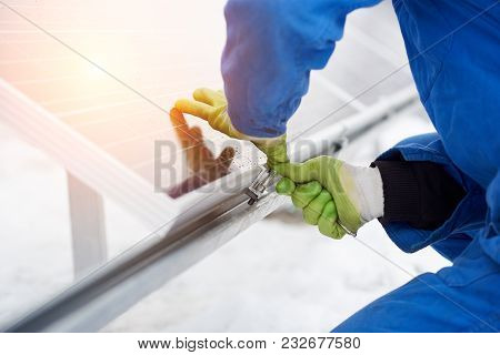 Engineers Installing Solar Panels. Worker With Tools Maintaining Photovoltaic Panels In Snow-covered