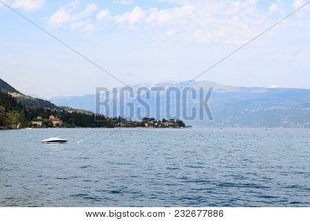 Lake Garda And Mountain Panorama With Boat In Salo, Italy