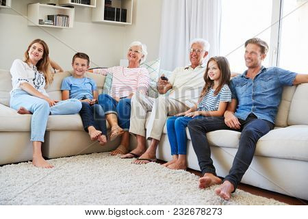 Multi Generation Family Sitting On Sofa At Home Watching TV