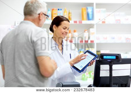 medicine, healthcare and technology concept - happy apothecary and senior male customer with digital prescription on tablet pc computer screen at pharmacy