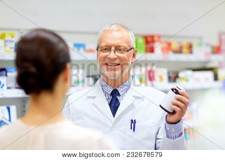 medicine, healthcare and people concept - senior apothecary with drug and female customer at pharmacy