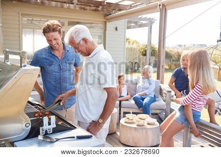 Multi Generation Family Enjoying Cooking Barbecue At Home