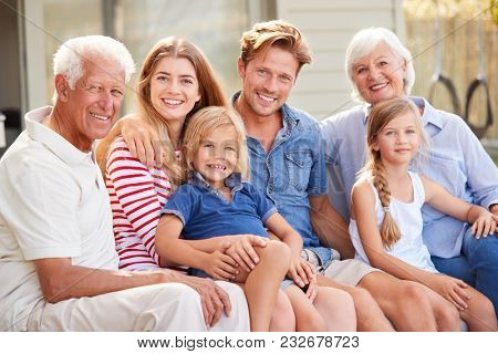 Portrait Of Multi Generation Family Relaxing On Deck At Home