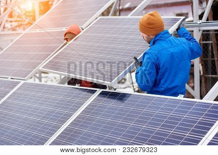 Technicians In Blue Suits Mounting Photovoltaic Solar Panels On Roof Of Modern House. Solar Modules
