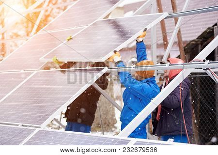Team Work. Technicians In Blue Suits Mounting Photovoltaic Solar Panels On Roof Of Modern House. Sol
