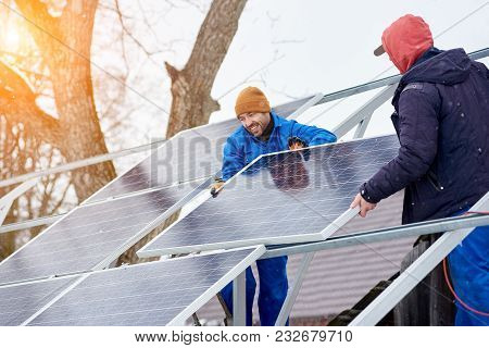 Smiling Technicians Mounting Blue Solar Modules On Roof Of Modern House As A Sustainable Source Of A