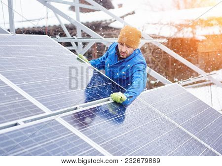 Strong Male Technician In Blue Suit Installing Photovoltaic Blue Solar Modules As Renewable Energy S