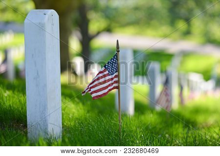 National flags ant headstones in Arlington National cemetery during Memorial Weekend - Washington DC, United States