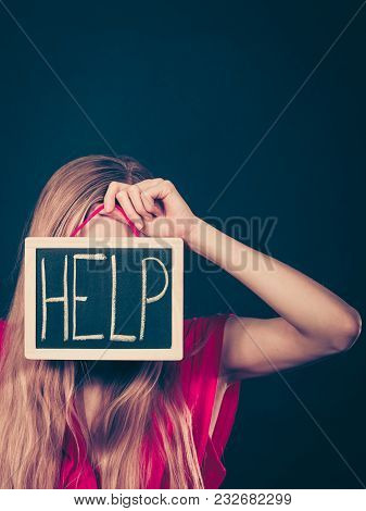 Suicidal Unrecognizable Skinny Woman Having Face Covered With Blonde Hair Holding Help Sign On Dark
