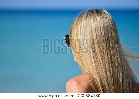 Closeup Of Blond Hair Girl Looking Something In The Distance With Wind In Her Hair. Woman Body Part