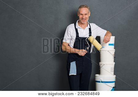 Smiling painter holding a paint roller and leaning on stack of paint bucket. Portrait of happy mature man looking at camera isolated over grey wall. Satisfied handyman with copy space.