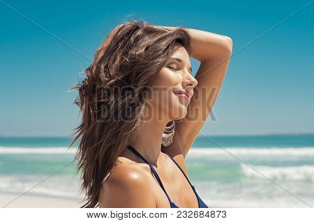 Closeup face of young woman with eyes closed enjoying breeze at beach. Portrait of carefree girl relaxing at sea. Beautiful smiling woman enjoying at beach the sun.