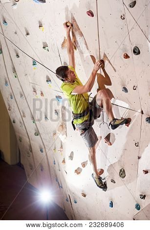 Push Yourself Higher. Strong Sportsman Climbing Artificial Wall In Bouldering Gym Indoors. Reaching