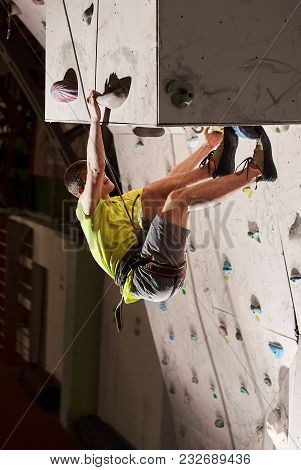 Active Boy Practicing Rock-climbing On A Rock Wall Indoors. The Concept Of Sport And Health At Any T