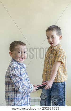 The Boy Shares A Toy With A Friend. Two Cheerful Little Boys. Two Brothers. Boys In Plaid Shirts