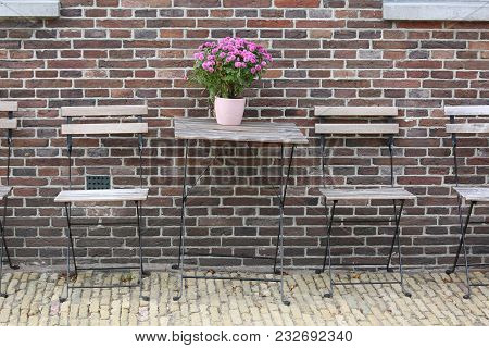 Ceramic Vase With Pink Flowers On A Wooden Table In A Bar