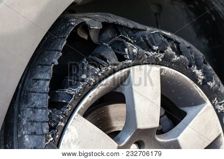 Close up details of a blown out tire with exploded, shredded and damaged rubber on a modern suv automobile. Flat low profile tyre on an alloy rim, ripped open in pieces with visible interior.