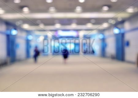 Background Blur Bright Blue Tones. Walkway Inside The Building There Are People.