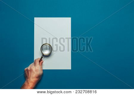 Hand Of Man With Loupe And Blank Sheet Of Paper On A Blue Surface, Top View Point Of View. Office Sp