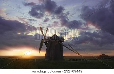 Windmill At Sunrise In Netherlands. Beautiful Old Dutch Windmill, Green Grass, Fence Against Colorfu