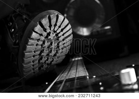 Combat Boot Stepping On A Bass Guitar. Hard Rock And Heavy Metal Concept