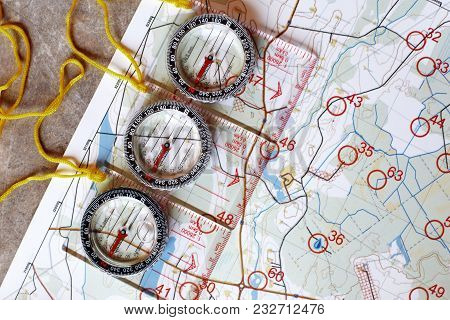 Several Plastic Transparent Compasses With Ruler For Orienteering Or Rogaining Sport On Color Topogr