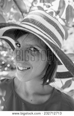 Greyscale Image Of A Smiling Woman In An Elegant Straw Sunhat Under The Shade Of A Tree In Summer.