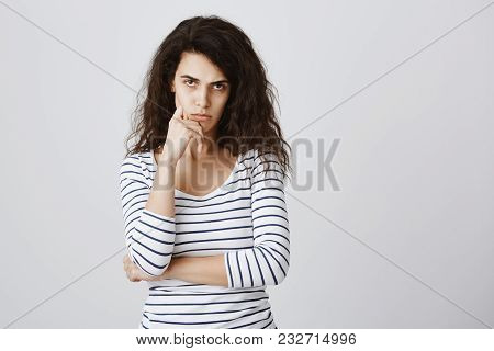 Studio Portrait Of Offended Cute Curly-haired Female Looking From Under Forehead, Holding Hand On Ch