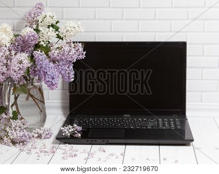 Beautiful White And Violet Lilac Flowers Bouquet In Glass Vase With Opened Black Laptop On The White
