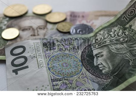 One Hundred Polish Zloty Banknotes With Coins. Closeup Photo