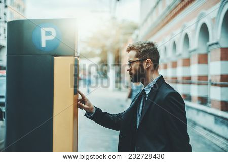 Bearded Serious Man Entrepreneur In Eyeglasses And A Formal Suit Is Using Parking Pay Station Termin