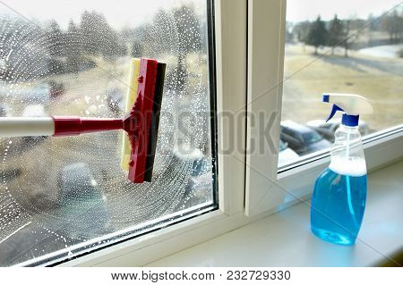 Glass Squeegee And Bottle Of Window Cleaner. Cleaning Windows With A Squeegee.