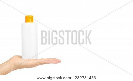 Plastic White Shampoo Bottle With Orange Cap In Hand Isolated On White Background. Gel Dispenser For