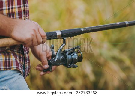Close Up A Man Holds And Untwists A Fishing Reel In His Hands On A Blurry Brown Background. Lifestyl