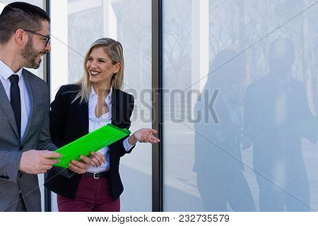 Businessman And Businesswoman Discussing Work While Walking. Busines Concept
