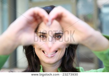 A pretty smiling woman forming a heart with her hands