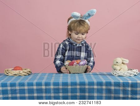 Kid With Easter Egg Hunt. Child With Bunny Ears Searching For Colorful Eggs At Home. Toddler Boy Pre