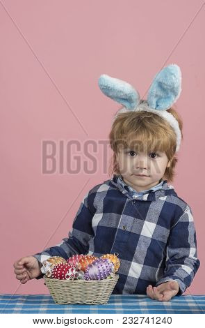 Easter Background. Cute Glance From Little Child Standing At The Table Covered With Blue Tablecloth.
