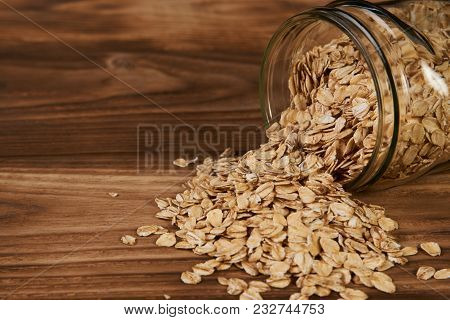 Oatmeal Glass Jar On Wooden Background. Glass Jar With Oatmeal Flakes, Close-up. Scattered Oat. Dry,